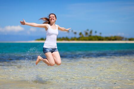 Happy beautiful woman jumping on tropical beach photo