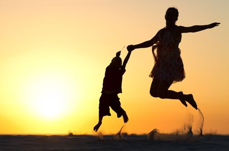 woman freedom: Mother and son silhouettes jumping on beach at sunset Stock Photo