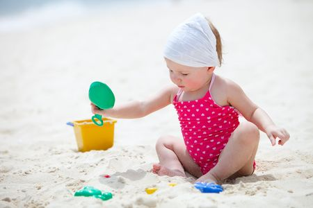 Adorable toddler girl playing with toys on tropical beach photo
