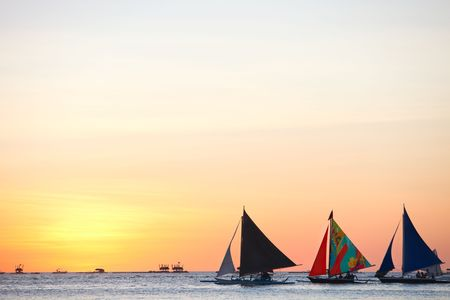Three sailboats against beautiful sunset Stock Photo