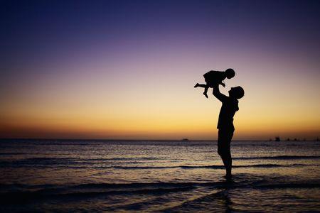 Otec a malá dcera siluety na pláži při západu slunce