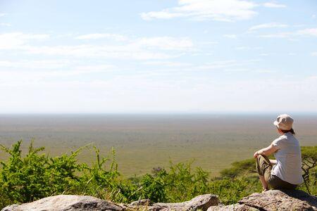 adventurous: Young woman observing beautiful national park of Serengeti in Tanzania Stock Photo