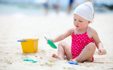 baby girl playing: Cute baby girl playing with beach toys on tropical beach