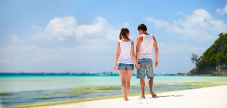 Panorama of romantic couple on white sand beach Stock Photo