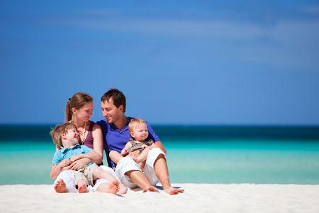 klein meisje op strand: Familie van vier plezier op tropische strand