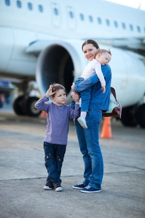 airplane girl: Young mother with two kids in front of airplane Stock Photo