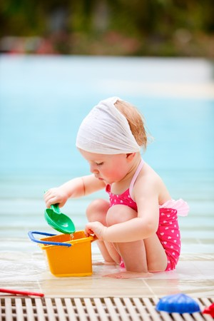 Adorable toddler girl playing in swimming pool photo