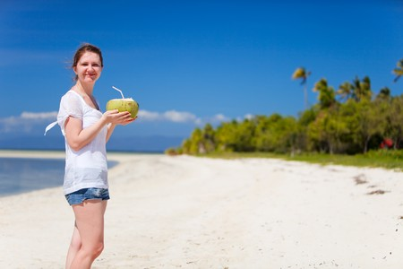 Portrait of young happy girl with coconut photo