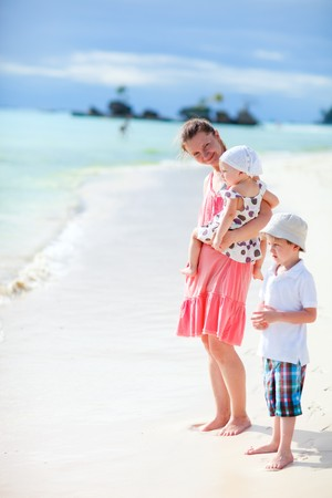 Young mother with her two kids on tropical beach vacation photo