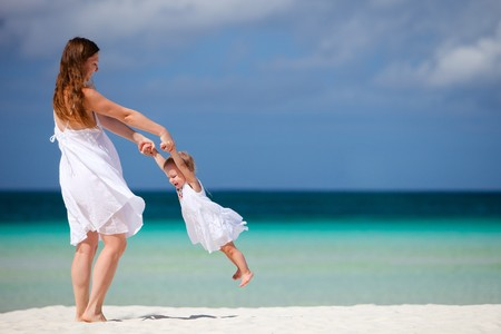 mum and daughter: Young mother and her little daughter having fun on tropical white sand beach Stock Photo