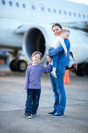 Young mother with two kids in front of airplane Stock Photo - 7036922