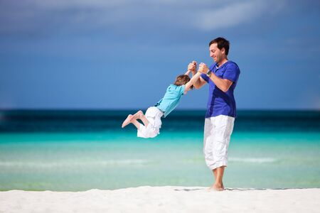 father with children: Father and son having fun on tropical white sand beach