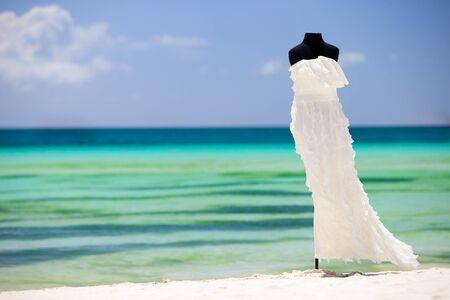 Beautiful wedding dress on white sand tropical beach photo