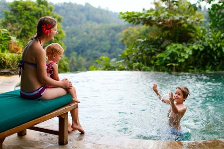 Mother and two kids playing in swimming pool photo