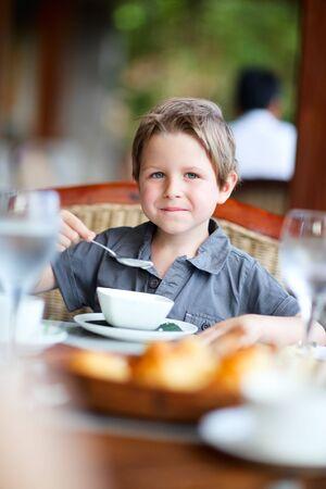 ni�os comiendo: Ni�o lindo tener delicioso desayuno  Foto de archivo