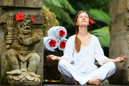 bali: Young woman doing yoga outdoors in tranquil environment