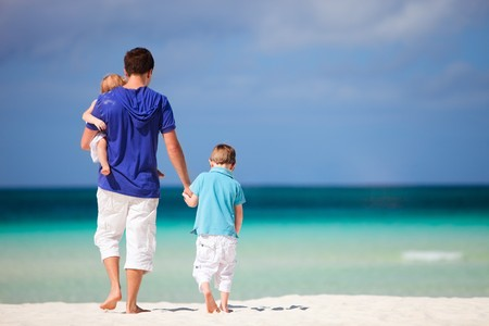 Happy father with his two kids on tropical beach vacation photo
