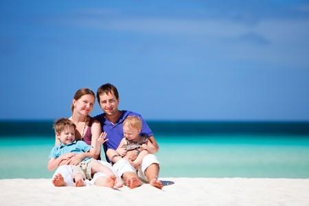 Family of four having fun on tropical beach photo