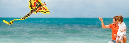 kite flying: Panorama of happy dad and son flying a kite together  Stock Photo