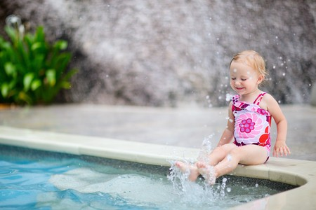 Cute toddler girl playing in swimming pool photo