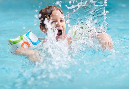 Cute boy splashing in swimming pool photo