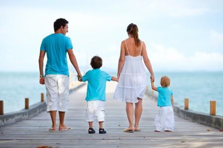 Familie van vier op houten steiger aan zee