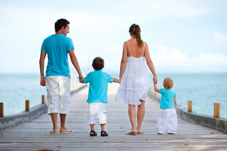 Family of four on wooden jetty by the ocean Stock Photo - 7406924