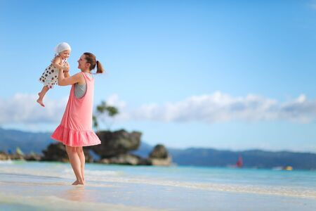 Young mother and her little daughter on tropical white sand beach photo