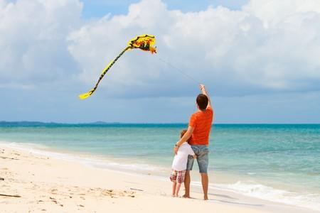 papalote: Joven padre y su hijo que se ejecutan con cometa en la playa