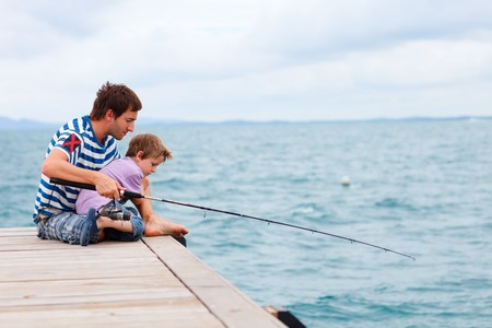 Father and son fishing together by the ocean