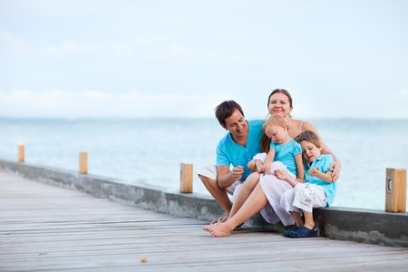 Family of four sitting on wooden jetty by the ocean photo