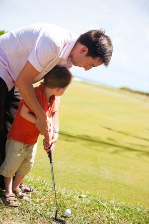 Father teaching his son to play golf photo