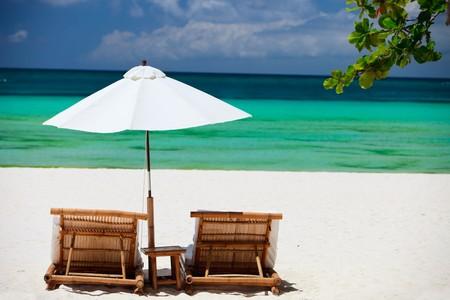 Beach chairs on perfect tropical white sand beach photo