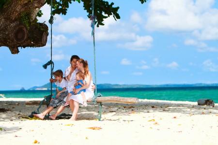 熱帯のビーチで楽しんで 4 人家族 写真素材