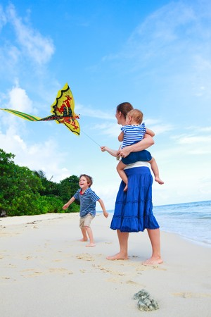 Young mother and two kids running with kite on the beach photo