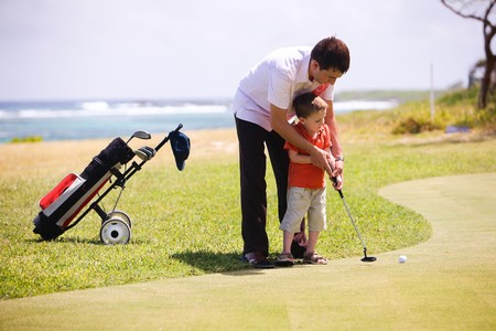 golf green: Father teaching his son to play golf