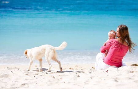 exotic pet: Young mother and her baby daughter on tropical white sand beach looking to dog Stock Photo