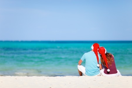 tropical christmas: Back view of young romantic couple in red Santa hats sitting on tropical white sand beach
