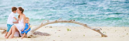 Panoramic photo of young beautiful woman with two kids sitting on tropical beach Stock Photo - 7598294
