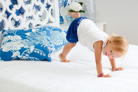 Portrait of adorable playful toddler girl jumping on bed in nicely decorated bedroom photo