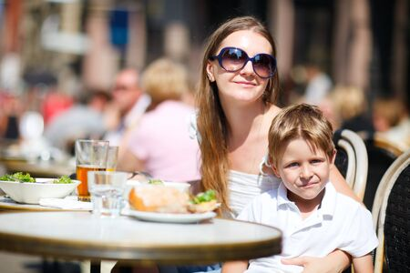 Young mother and her son having lunch in outdoor restaurant on summer day  photo