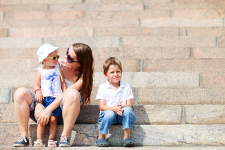 Young mother and two adorable kids sitting outdoors on stairs on summer day photo
