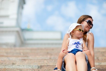 Young mother and her adorable little daughter enjoying day out in city on summer day photo