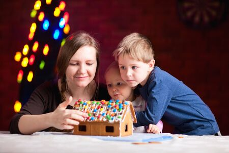 Young mother and two kids making gingerbread house on Christmas eve photo
