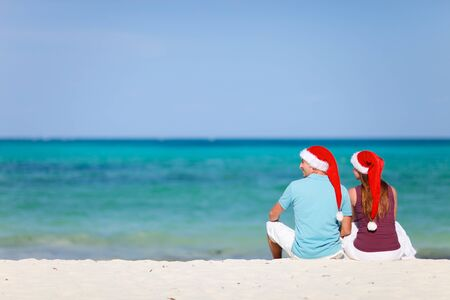 Young couple wearing red Santa hats on  Christmas beach vacation photo