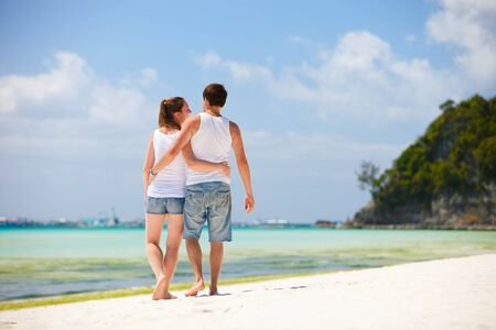 Back view of young romantic couple walking along tropical beach photo