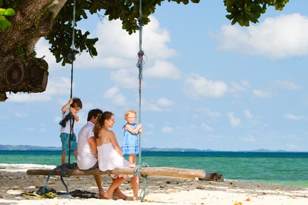 Young beautiful family swinging on tropical beach Stock Photo