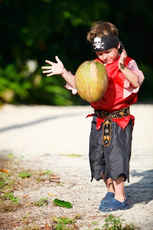 Boy dressed in pirate costume throwing coconut photo