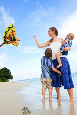 Mother and two kids flying kite on tropical beach photo