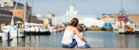Panoramic photo of mother and son sitting on jetty and enjoying beautiful views central Helsinki Finland